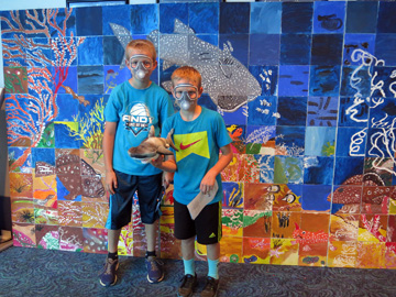 Two young boys wearing paper scuba masks pose in front of a sanctuary mural with a plush shark toy
