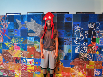A man wearing a paper scuba mask and a red squid hat poses in front of the sanctuary mural