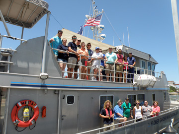 A group photo of turtle release participants standing on the lower and upper decks of R/V MANTA once it returned to the dock