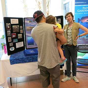 A father holds a young child while talking to a volunteer in front of a table display about conservation