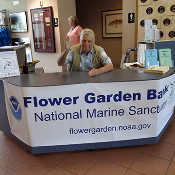 A man waves from behind the entry desk with a Flower Garden Banks National Marine Sanctuary banner in front of him