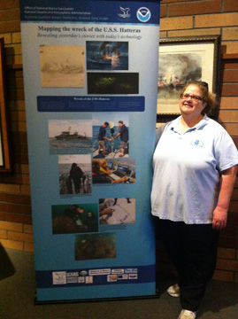 Shelley DuPuy standing next to our new pop-up banner about the USS Hatteras