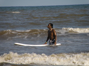 Basir in the water with a surfboard floating alongside him.