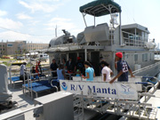 Students crossing the gangway from the dock onto the R/V Manta.