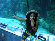 An excited student pointing at divers in the aqurium.