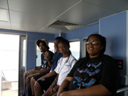 Students sitting on a bench in the pilot house of the R/V Manta.