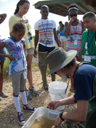 A volunteer tells students about what they caught.