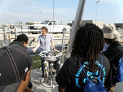 Students listening to a person explaining a large piece of equipment on the deck of a boat.