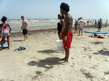 Students standing on beach holding a bucket for collecting trash.