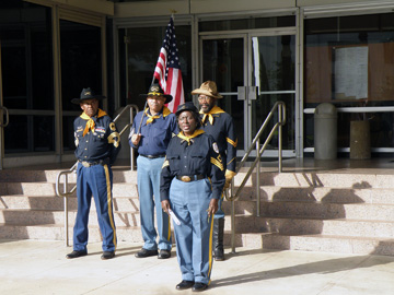 Four Buffalo Soldier re-enactors standing with an American flag in front of courthouse steps