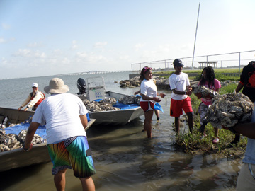 Students loading bags of oyster shell onto two small boats.