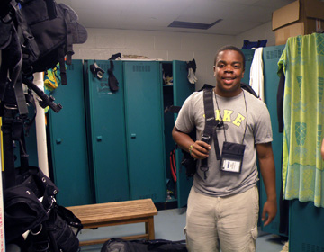 A student in a locker room area with dive gear slung over one shoulder.