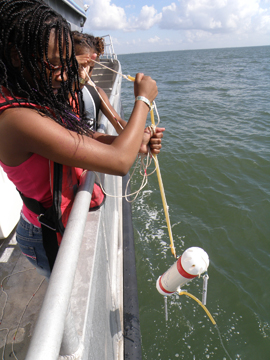 Girls pulling up a niskin bottle from the water after taking a sample.