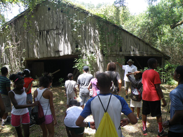 Students standing outside an old wooden barn that looks like it is about to collapse.