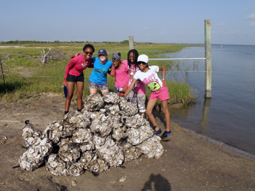 Students gathered around a pile of oyster shell sacks they just unloaded by the water.