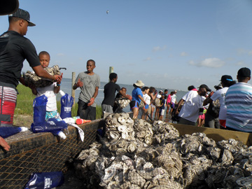 Students passing bags of oyster shell from one to the next to load them on a boat.
