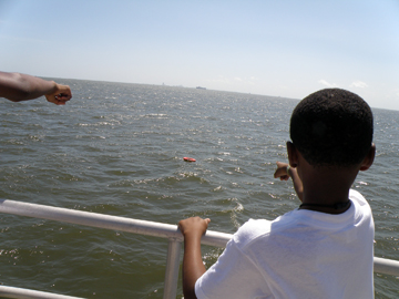 Student pointing at floating lifesaving ring behind the boat.
