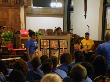 Two students holding up a quilt in front of a church audience.