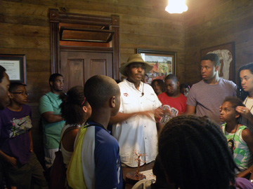Sam Collins III talkikng to a group of students inside one of the wood-paneled rooms of an historic house.