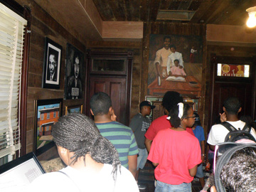 A group of people inside a wood paneled room decorated with art representing African American history.