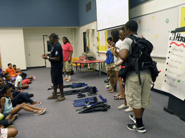 Students showing scuba equipment to other students seated on the floor in front of them.