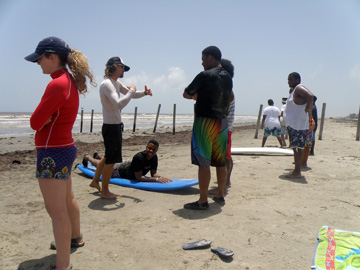 Student lying on surf board on beach while instructor explains surfing technique. Other students stand nearby watching.