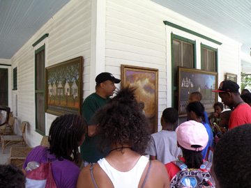 A gentleman explaining paintings displayed on the front porch of an historic house.