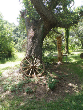 An old wooden wagon wheel leaning up against the trunk of a tree.