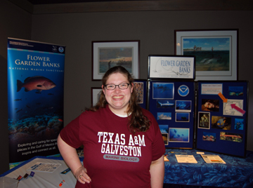 Andrea, a sanctuary volunteer, standing in front of the display proudly wearing her Texas A&M Galveston Marine Biology shirt