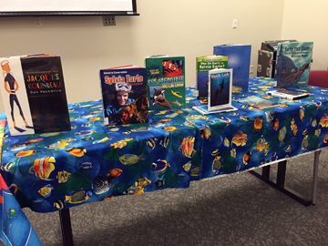 A table covered with a colorful fish fabric displays kids books about oceans and ocean heroes.