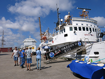 A table with a blue tablecloth sits on the dock next to NOAA ship Oregon II. Guests stand to the left of the ship's gangway waiting to board