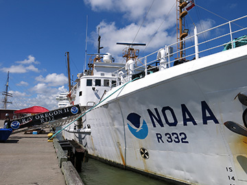Looking down the starboard side of NOAA ship Oregon II from bow towards stern as it is docked at Pier 21 in Galveston. A gangway leads from the ship to the pier for pedestrian access. NOAA R232 is visible next to the NOAA logo at the bow of the ship.