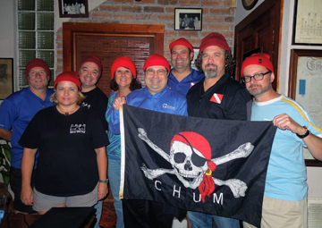 A group of dive club members wearing red watch caps and holding a pirate flag