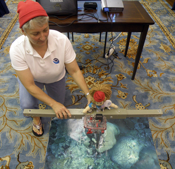 A woman and a doll, both wearing red hats, doing a reef monitoring demonstration with a t-frame