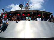 Group of students, some wearing red hats, on the observation deck of the R/V Manta.