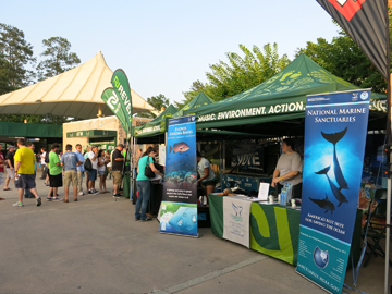The sanctuary's display booth under a green pop-up shelter that says Music. Environment. Action. Two sanctuary banners are displayed on either side of the shelter.