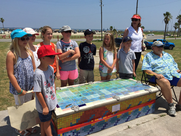 Jacqui, her students and Robert Webster posing around the finished bench