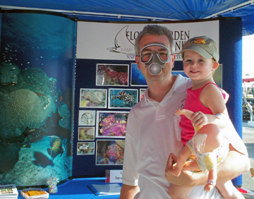 A man wearing a paper scuba mask while holding his daughter and standing in front of a sanctuary display board.