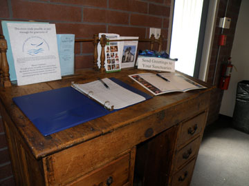 Wooden captain's desk with a sign-in log and an anniversary card for people to sign.
