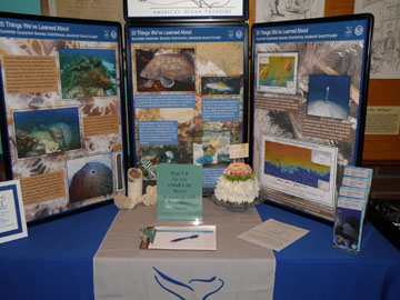 Table top display about Flower Garden Banks National Marine Sanctuary with a cake-shaped flower arrangement in front of it.