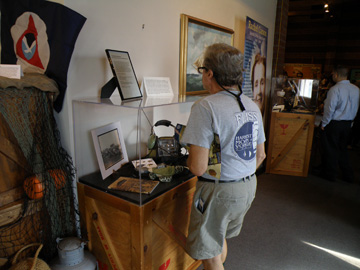 A guest views a display case of information about sea turtle research.