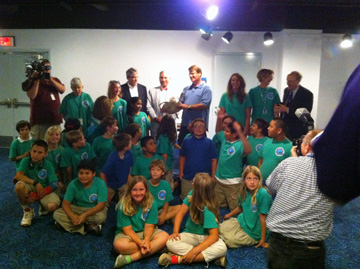 Group photo of students, Galveston Mayor, Senator Larry Taylor, Ben Higgins, a sea turtle, and a few teachers