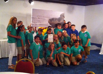 Group of students and a teacher posing with a large image of a Kemp's Ridley sea turtle