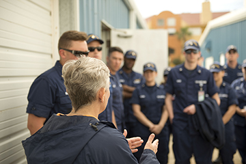 Looking from behind Kelly Drinnen at a group of Coast Guard staff in uniform as Kelly explains what they are about to see in the turtle barn.