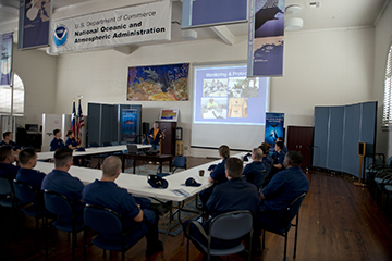 Coast Guard staff seated around tables watching a Powerpoint presentation in a large room