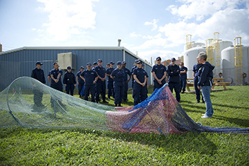 Group of Coast Guard staff, in uniform, standing behind a shrimp net with TED installed, on the lawn by the turtle barn.