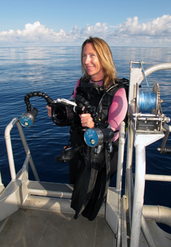 Emma Hickerson standing at the back of a boat holding her underwater video camera