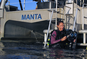 Emma on the dive ladder of R/V MANTA with her underwater video gear