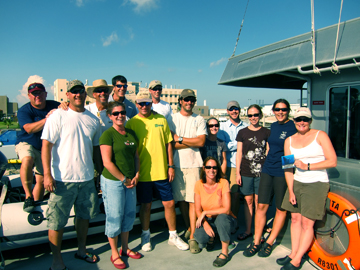 The full group of researchers standing on the deck of the boat