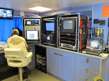 A man sits in front of a bank of monitors and controls to operate an ROV